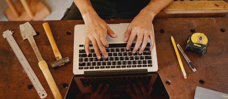 faceless artisan typing on laptop in workshop