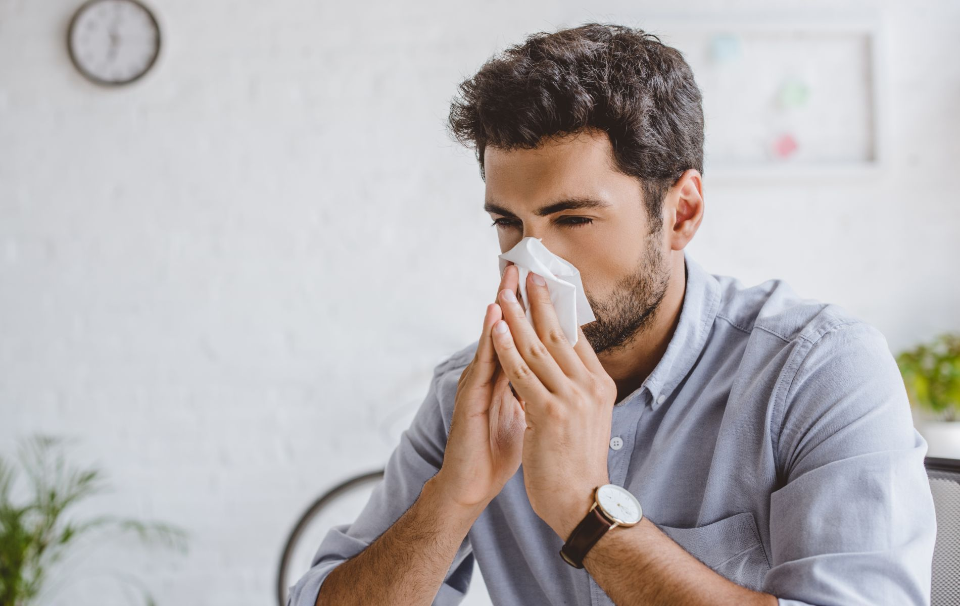 man blowing is noes from allergies
