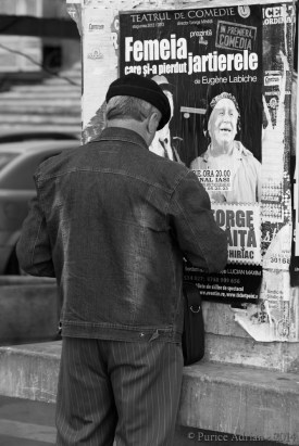 old guy in front of a theater poster