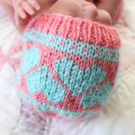 Newborn baby in hand knit pink and blue hearts hat from twin baby shower gift set. Handmade by Liz @PurlsAndPixels.