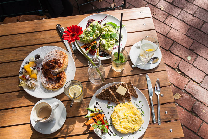 Full breakfast table with pancakes, scrambled egg and avocado baguette in Hamburg at Von der Motte