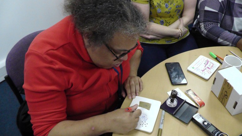 Picture shows Sam creating a purpleSTARS card with the Suitcase Story Passport Stamp