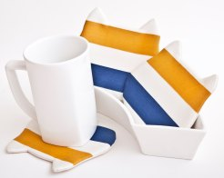 Still life of 3 cat shaped cup coasters colored with yellow, blue and white stripes, with a white cup on a side.
