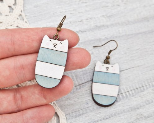 Still life of a pair of cat shaped earrings colored in light blue and white.