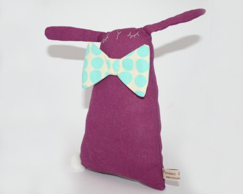 Still life picture of a purple bunny soft toy with a giant dotted papillon.