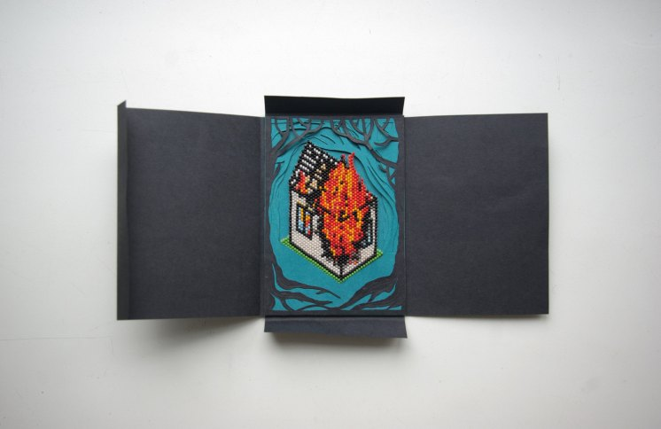 Still life photo of a beaded reproduction of a burning house inside a black paper box seen from above.