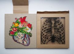 Still life photo of a beaded flowers and heart necklace on a paper box with a paper torso skeleton seen from above.