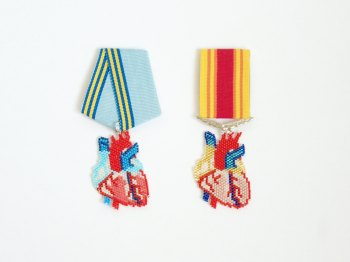 Still life photo of two beaded medal anatomical hearts brooch