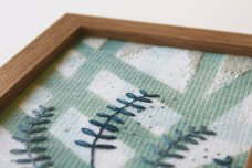 Still life photo of a framed abstract textile art with geometric forms, detail view.