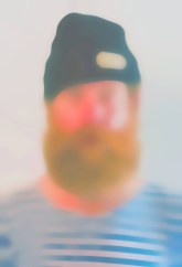 Blurry portrait of a man with a striped T-shirt, a beard and a hat.
