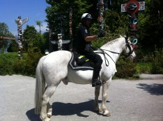 A policeman on a horse that goes around Stanley Park