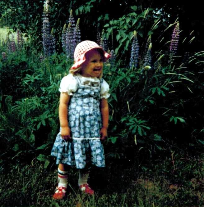Tyttö ja lupiinit puutarhassa.