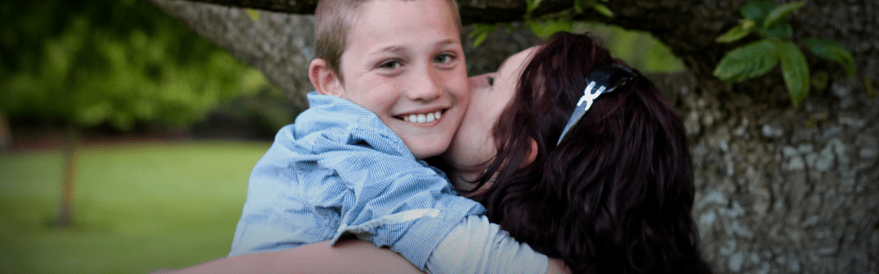 Photograph of a boy and his mother sharing a loving hug