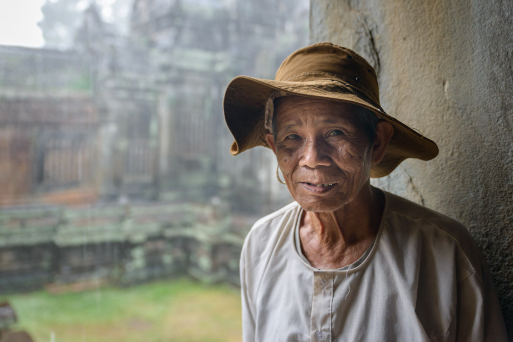 An old man waits out the rain, in a temple inside the Angkor complex, Cambodia.