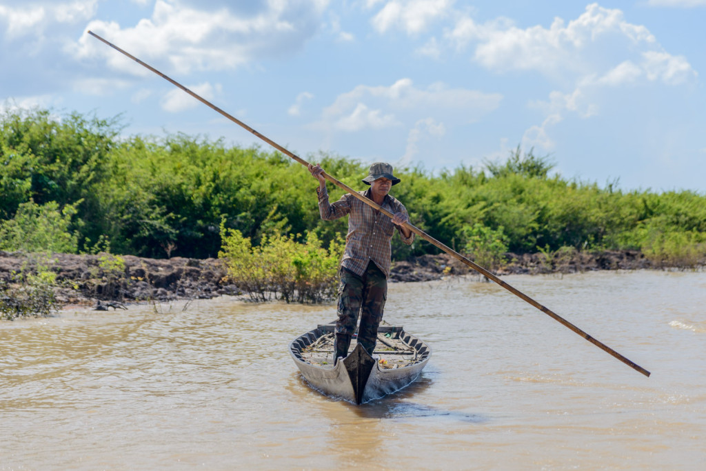 A man pushes himself and his boat along a river tributary, outside Siem Reap, Cambodia.