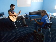 picture of a teacher with his guitar student
