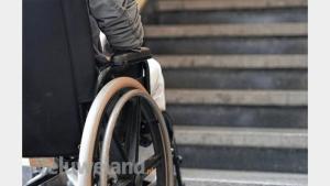 Een persoon in een handbewogen rolstoel
