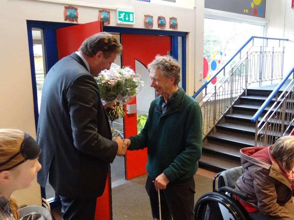 De burgemeester geeft tijdens een bezoek aan het Scholenproject een hand aan de secretaresse van de Plaatselijke Werkgroep Toegankelijkheid.