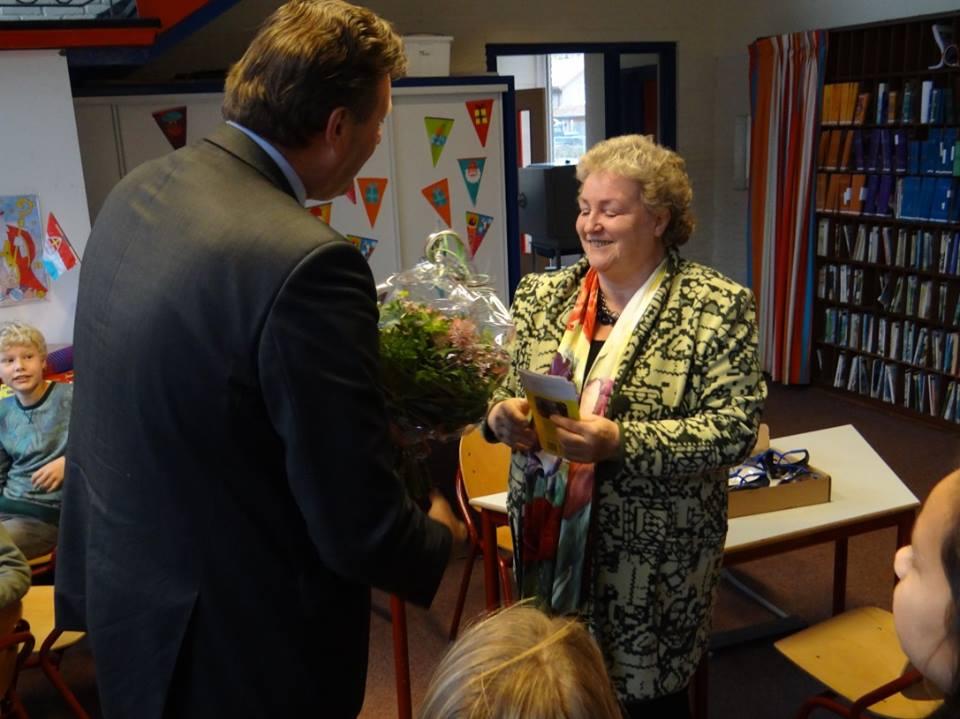 De burgemeester overhandigd een bos bloemen aan de secretaresse van de Plaatselijke Werkgroep Toegankelijkheid Nunspeet/
