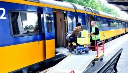 NS treinstel op het perron waar assistentie aanwezig voor mensen met een beperking.