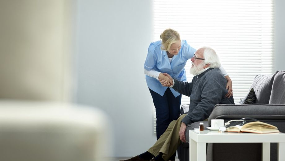Afbeelding van een thuishulp bij een patiënt.