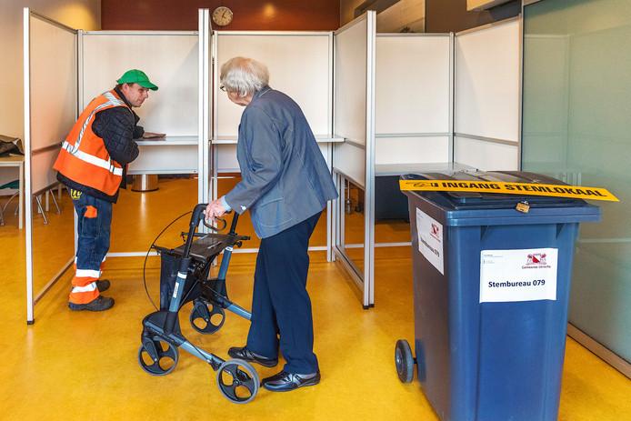 Man met rollator in een stemlokaal.