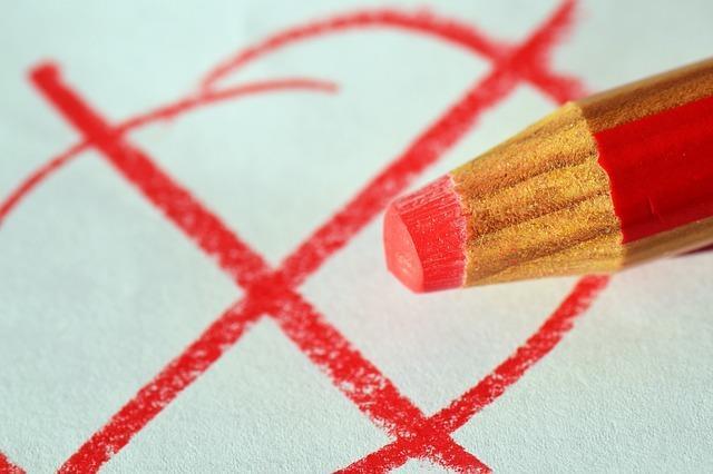 Afbeelding van rood potlood en een rood kruisje op papier.
