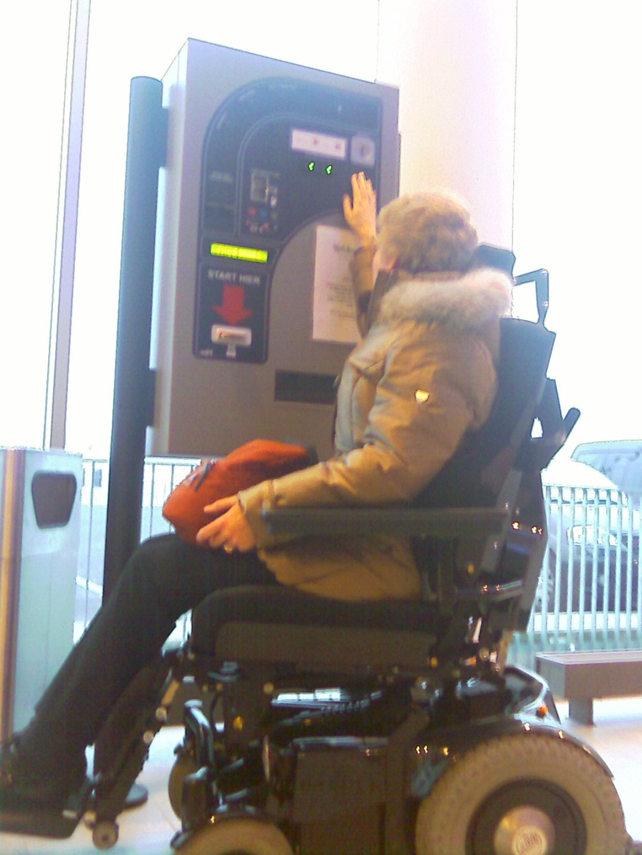 Afbeelding van een man in een scootmobiel bij een parkeerautomaat.