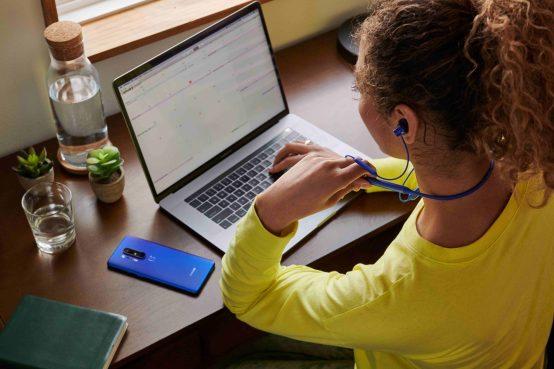 OnePlus Bullets Wireless Z écouteurs. Personne sur son ordinateur avec téléphone OnePLus déposé sur la table