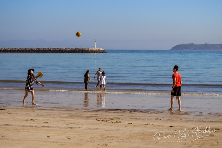 A mother and son playing rackets on the beach