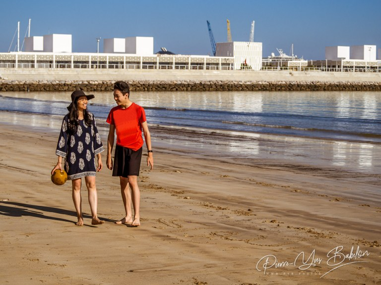 A mother and son playing ball on the beach