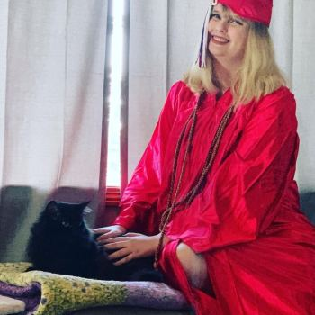 em in a grad robe with her black cat