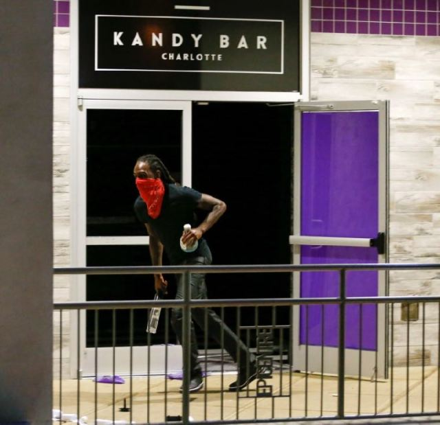 A looter grabs liquor bottles from the club Kandy Bar in uptown Charlotte, NC during a protest of the police shooting of Keith Scott, in Charlotte, North Carolina, U.S. September 21, 2016. REUTERS/Jason Miczek
