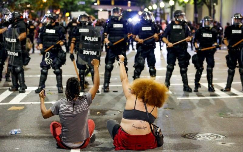 Two people sit on the ground as they protest in front of police in uptown Charlotte, NC  during a protest of the police shooting of Keith Scott, in Charlotte, North Carolina, U.S. September 21, 2016. REUTERS/Jason Miczek