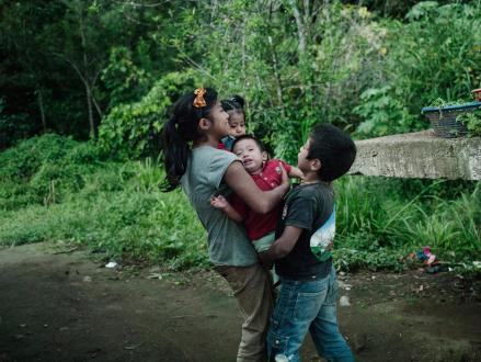 Lilian and her brother play with her son Luis David and their cousin who is also a baby. Twelve years old when she became a mother, she clims trees, plays soccer and steals fruit from a neighbors trees whenever she is relieved of her obligations as a mother.