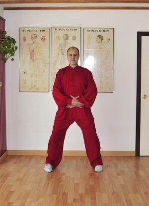 Daoyin Wuji poste natural abierto con las manos superpuestas sobre Dantian.