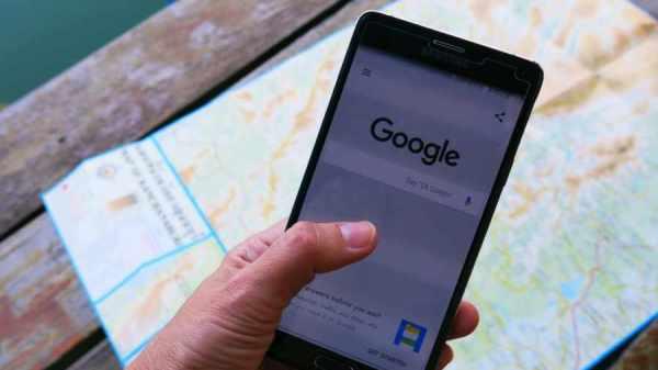 Persona con teléfono en la mano y un mapa de fondo