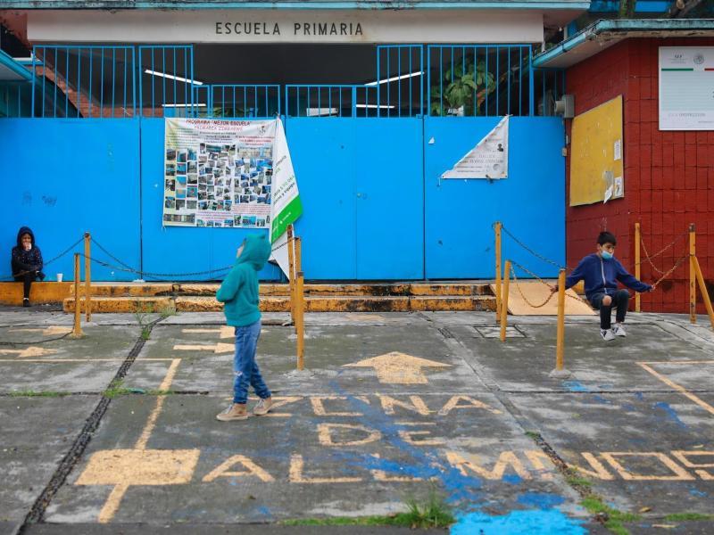 Niños juegan frente a un colegio cerrado, el 5 de agosto de 2021, en la Ciudad de México (México). EFE/ Carlos Ramírez