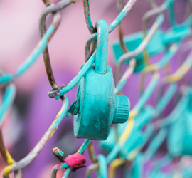 turquoise lock on a chain mail fence with a purple background signifying unlocking sexual violence