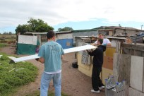 Peter, Bobby, & Ryan moving corrugated tin to repair roofs.