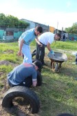 Evan, Peter, & Ryan putting concrete into tires.