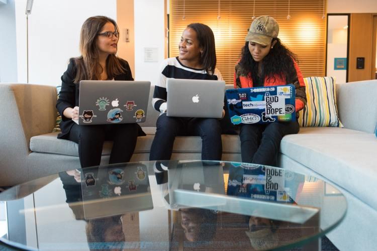 Chicas conversando con laptops