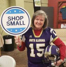 """Artist Sonya Gordon wants to score a win for her small business on Iron Bowl Saturday, which is also Small Business Saturday. She invites shoppers to visit High Cotton Arts before the game and wear their favorite team colors. She is sporting UNA gear because she wants """"Auburn and Alabama fans to feel welcome to shop with us."""""""