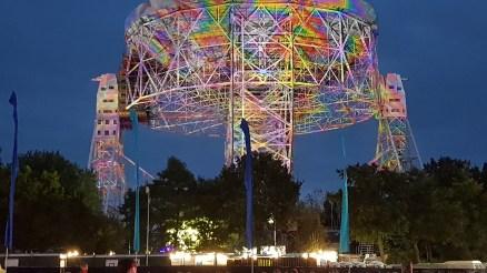 The huge Lovell radio telescope dish at night illuminated by multicoloured lights