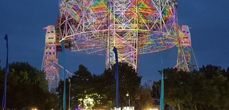 The huge Lovell radio telescope dish at night illuminated by multicoloured lights