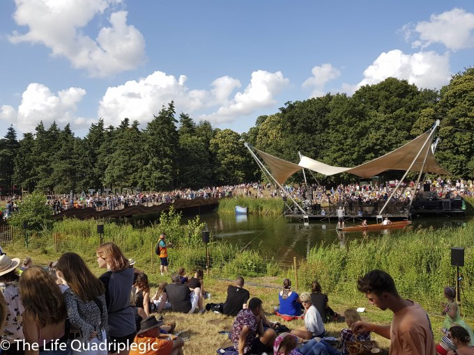 In the foreground people relax on the grass next to a lake. A stage is built over the lake and a crowd is assembled on the far shore