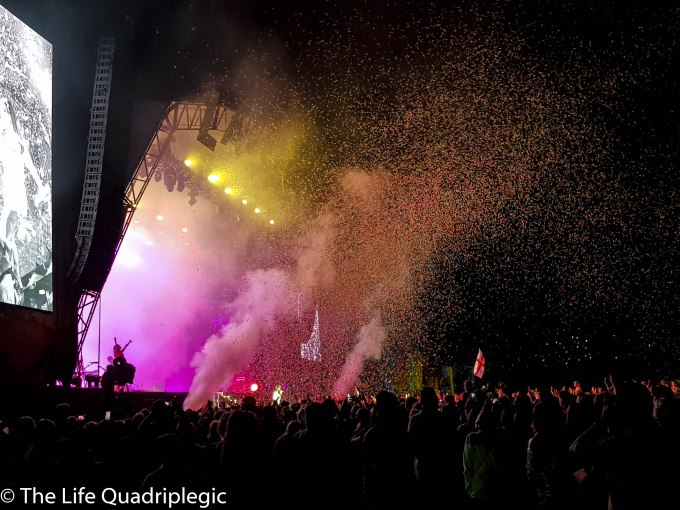 A large crowd is stood in front of a stage at night with lots of multicoloured confetti floating in the air above them