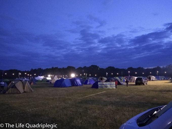 A night time shot lots of tents in a grassy field with a line of trees in the background