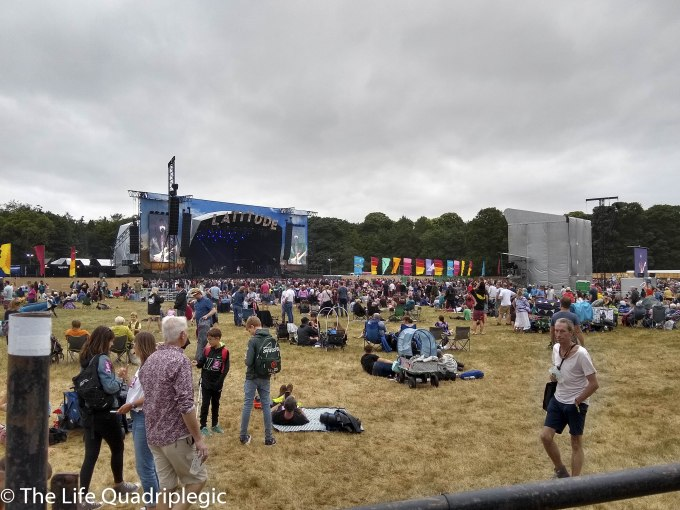 A large stage is in the background with a line of trees behind it. In front of the stage there is a large crowd relaxing in a grassy field