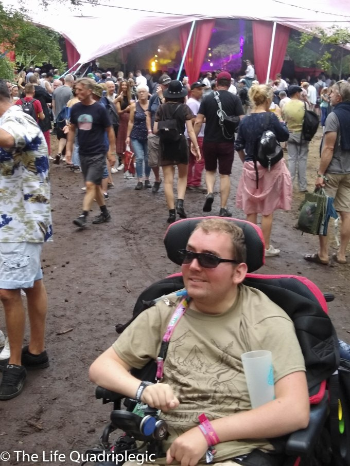 A young man in a powerchair smiles at the camera with a crowd of people walking towards a stage in the background